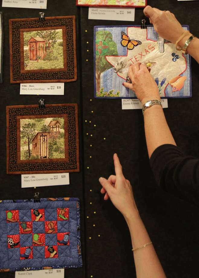 Quilters from Canada, U.S., UK, India, and Australia donated small quilts to the Alzheimer's Art Quilt Initiative to fundraise for research Alzheimers by selling quilts at the International Quilt Festival at the George R. Brown Convention Center on Wednesday, Oct. 31, 2012, in Houston. Photo: Mayra Beltran, Houston Chronicle / © 2012 Houston Chronicle