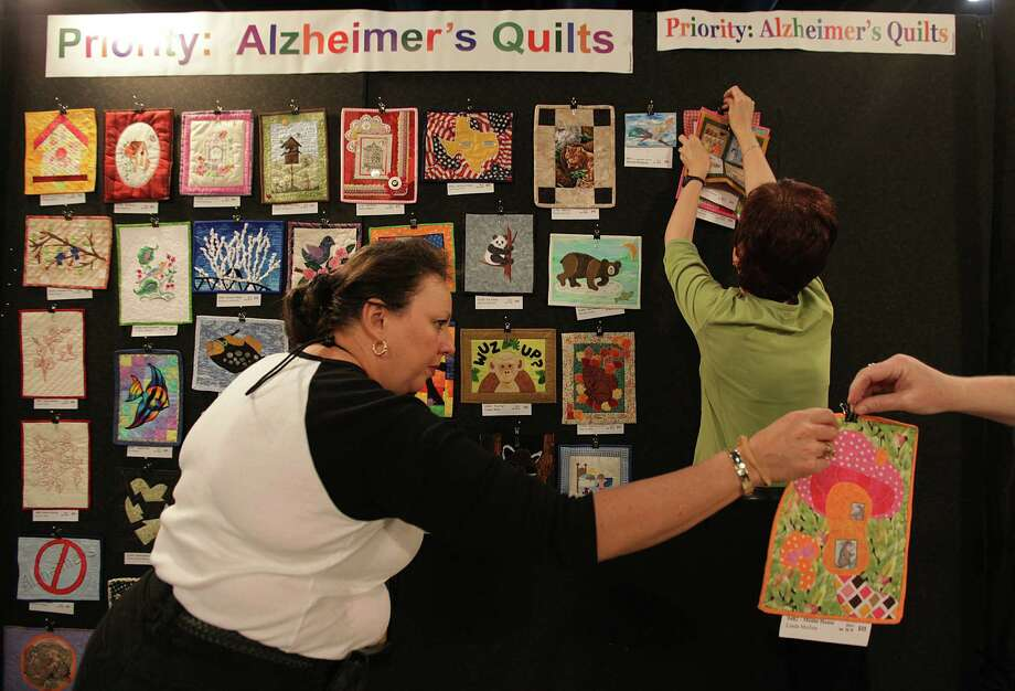Niki Gottesman takes a quilt to hang in the Alzheimer's Art Quilt Initiative booth which is on display and quilts for sale at the International Quilt Festival at the George R. Brown Convention Center on Wednesday, Oct. 31, 2012, in Houston.  All proceeds to be donated for Alzheimer's research. Photo: Mayra Beltran, Houston Chronicle / © 2012 Houston Chronicle