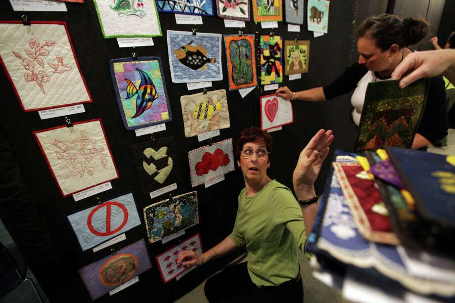 Ami Simms, Founder and Executive Director of Alzheimer's Art Quilt Initiative, quickly hangs quilts in their booth to sell during the International Quilt Festival at the George R. Brown Convention Center on Wednesday, Oct. 31, 2012, in Houston.  All proceeds to be donated for Alzheimer's research. Photo: Mayra Beltran, Houston Chronicle / © 2012 Houston Chronicle