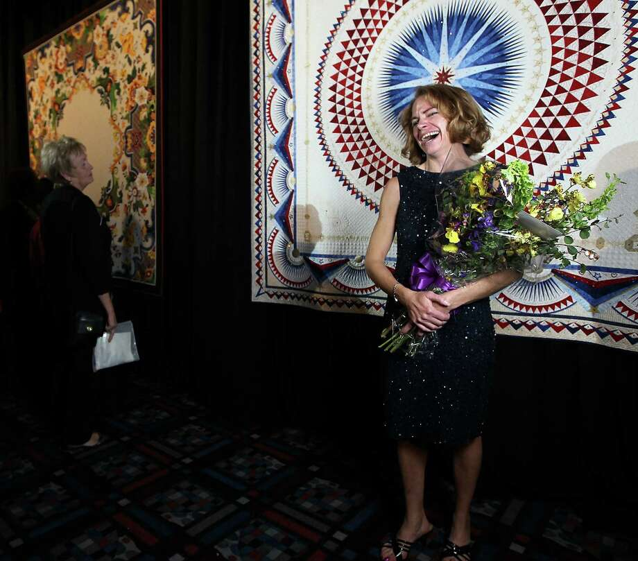 "Sherry Reynolds of Laramie, Wyoming reacts as she stands in front of her quilt ""America, Let it Shine"" after her quilt was announced as the Best of Show ( the $10,000 Handi Quilter Best of Show Award) at the International Quilt Festival at the George R. Brown, Tuesday, Oct. 30, 2012, in Houston. Photo: Karen Warren, Houston Chronicle / © 2012  Houston Chronicle"