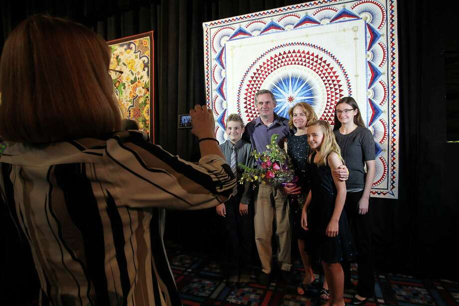 "Sherry Reynolds of Laramie, Wyoming with her family, husband Dan, and children Darryn, 11, and daughters Kara, 10, and Taylor, 13 as they stand in front of her quilt ""America, Let it Shine"" after her quilt was announced as the Best of Show ( the $10,000 Handi Quilter Best of Show Award) at the International Quilt Festival at the George R. Brown, Tuesday, Oct. 30, 2012, in Houston. Photo: Karen Warren, Houston Chronicle / © 2012  Houston Chronicle"