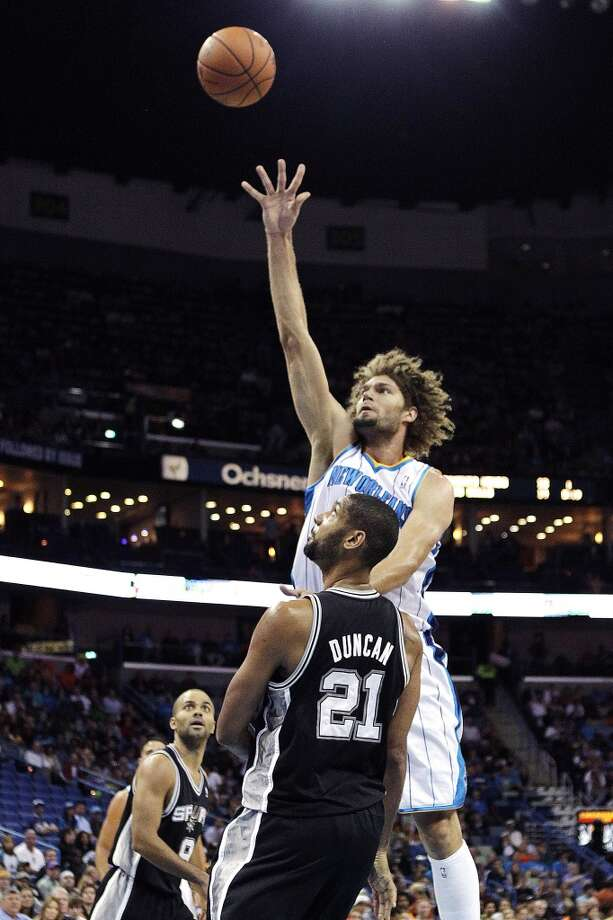New Orleans Hornets center Robin Lopez shoots over San Antonio Spurs power forward Tim Duncan (21) in the first half of an NBA basketball game in New Orleans, Wednesday, Oct. 31, 2012. (AP Photo/Gerald Herbert) (Associated Press)