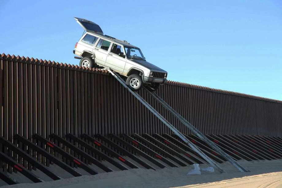 A Jeep Cherokee driven by suspected smugglers is stuck atop the border fence near Yuma, Ariz. Photo: HOPD / U.S. Customs and Border Protecti