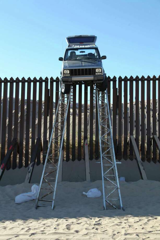 In this photo provided by the U.S. Customs and Border Protection, a silver Jeep Cherokee that suspected smugglers were attempting to drive over the U.S.-Mexico border fence is stuck at the top of a makeshift ramp early Wednesday, Oct. 31, 2012 near Yuma, Ariz. U.S. Border Patrol agents from the Yuma Station seized both the ramps and the vehicle, which stalled at the top of the ramp after it became high centered. The fence is approximately 14 feet high where the would-be smugglers attempted to illegally drive across the border. The two suspects fled into Mexico when the agents arrived at the scene. (AP Photo/U.S. Customs and Border Protection) Photo: HOPD / U.S. Customs and Border Protecti