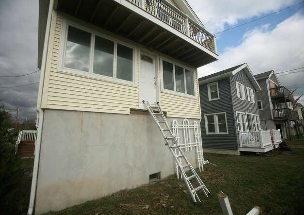 A ladder acts as a makeshift front stairway for a home damaged by Hurricane Sandy on Point Beach Road in Milford on Wednesday, October 31, 2012. Photo: Brian A. Pounds