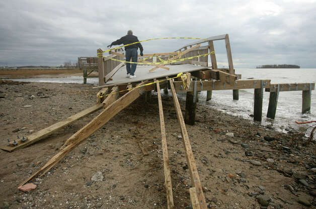 A man climbs on to the boardwalk, badly damaged by Hurricane Sandy, between Walnut Beach and Silver Sands State Park in Milford on Wednesday, October 31, 2012. Photo: Brian A. Pounds