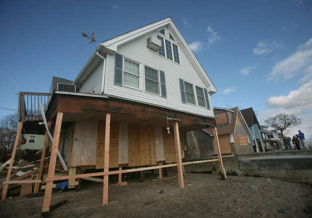 Lumber acts as temporary support for a waterfront home badly damaged by Hurricane Sandy on the Milford shore on Wednesday, October 31, 2012. Photo: Brian A. Pounds