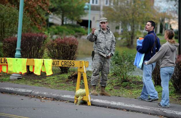 A member of the National Guard stops Dimitrie Hristo and his sister Crina Cody as they try to take a walk down Gilman Street near Saint Mary's By the Sea with 3-month-old Corinne Cody Wednesday, Oct. 31, 2012 in Bridgeport, Conn.  Access to the Saint Mary's By the Sea area of Bridgeport was limited to residents following Hurricane Sandy. Photo: Autumn Driscoll