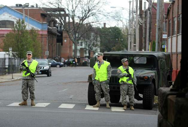 Members of the National Guard stand at the intersection of Warren Street and Railroad Avenue Wednesday, Oct. 31, 2012 in Bridgeport, Conn.  Access to the Seaside Park area of Bridgeport was limited to residents following Hurricane Sandy. Photo: Autumn Driscoll