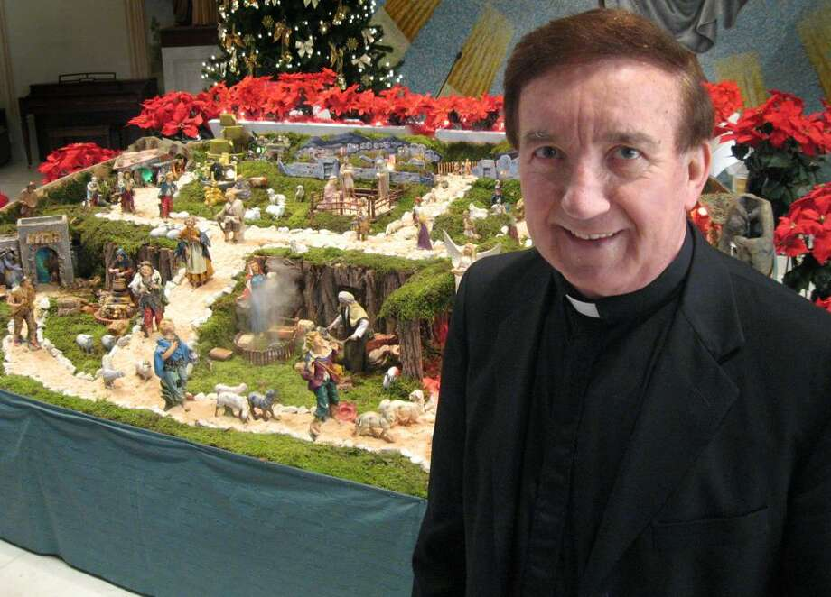 Msgr. Matthew Bernelli on St. Mary's Parish on Bridgeport's lower East Side stands before the nativity scene he assembles every year in the weeks prior to Christmas. Photo: John Burgeson / Connecticut Post