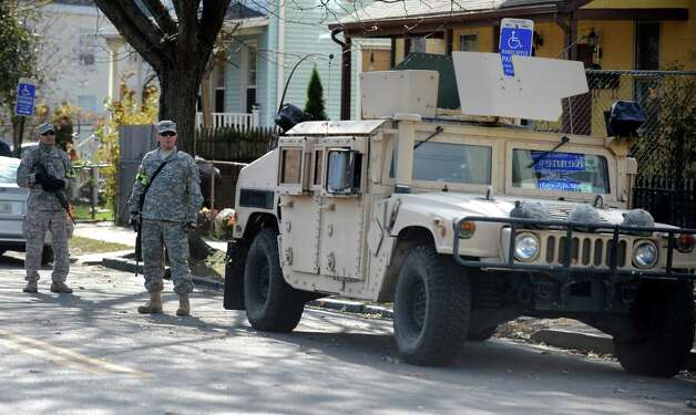 Members of the National Guard stand at the intersection of Lafayette Street and Railroad Avenue Wednesday, Oct. 31, 2012 in Bridgeport, Conn.  Access to the Seaside Park area of Bridgeport was limited to residents following Hurricane Sandy. Photo: Autumn Driscoll
