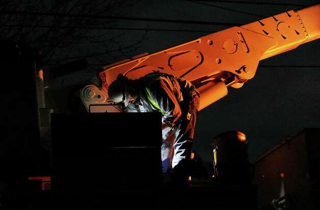 KCP&L crews, out of Kansas City, Mo., work to repair wires on Newfield Avenue between Case Road and Denicola Place in Stamford, Conn. on Wednesday, Oct. 31, 2012. Crews worked into the night in an effort to restore power to residents after severe damage from the effects of Hurricane Sandy left many in the city in the dark. Photo: Cathy Zuraw
