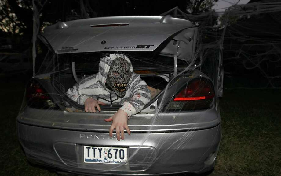 Phillip Melton, 20, lies in wait in the back of a car as he waits for trick-or-treaters in the New Territory subdivision on Halloween night, Wednesday, Oct. 31, 2012, in Sugar Land. Photo: Karen Warren, Houston Chronicle / © 2012  Houston Chronicle