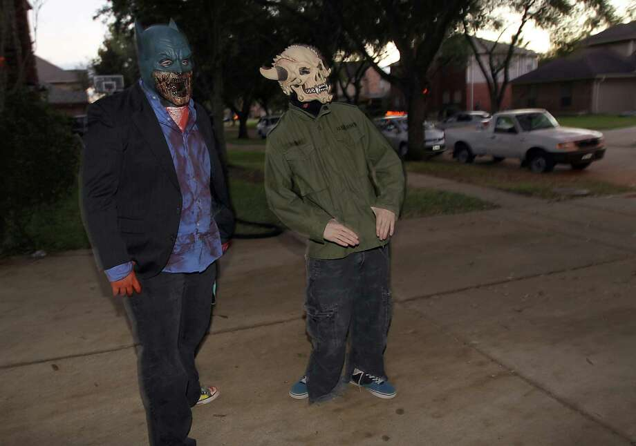 Tyler Quinn, 18, left, and Zachary Melton, 17, right, wait for trick-or-treaters in the New Territory subdivision on Halloween night, Wednesday, Oct. 31, 2012, in Sugar Land. Photo: Karen Warren, Houston Chronicle / © 2012  Houston Chronicle