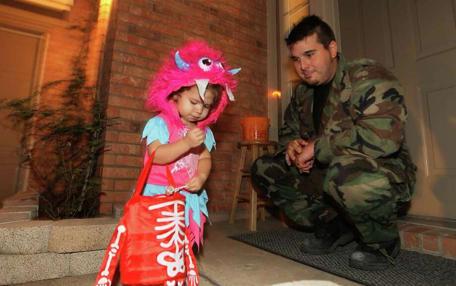 Keylee Melton, 18-months-old, puts candy in her bag as her dad, David Melton watches her trick-or-treat in the New Territory subdivision on Halloween night, Wednesday, Oct. 31, 2012, in Sugar Land. Photo: Karen Warren, Houston Chronicle / © 2012  Houston Chronicle