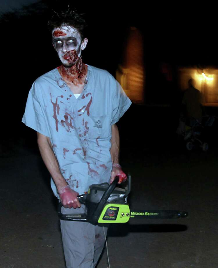 Clayton Dorsey walks his front yard as a zombie with a chainsaw as he waits for trick-or-treaters in the New Territory subdivision on Halloween night, Wednesday, Oct. 31, 2012, in Sugar Land. Photo: Karen Warren, Houston Chronicle / © 2012  Houston Chronicle