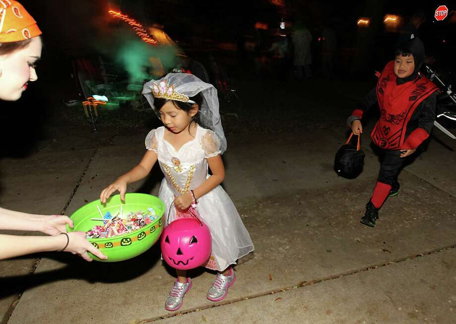 Sofia Ho, 5, gets candy from Nicole Dorsey as she goes trick-or-treating in the New Territory subdivision on Halloween night, Wednesday, Oct. 31, 2012, in Sugar Land. Photo: Karen Warren, Houston Chronicle / © 2012  Houston Chronicle