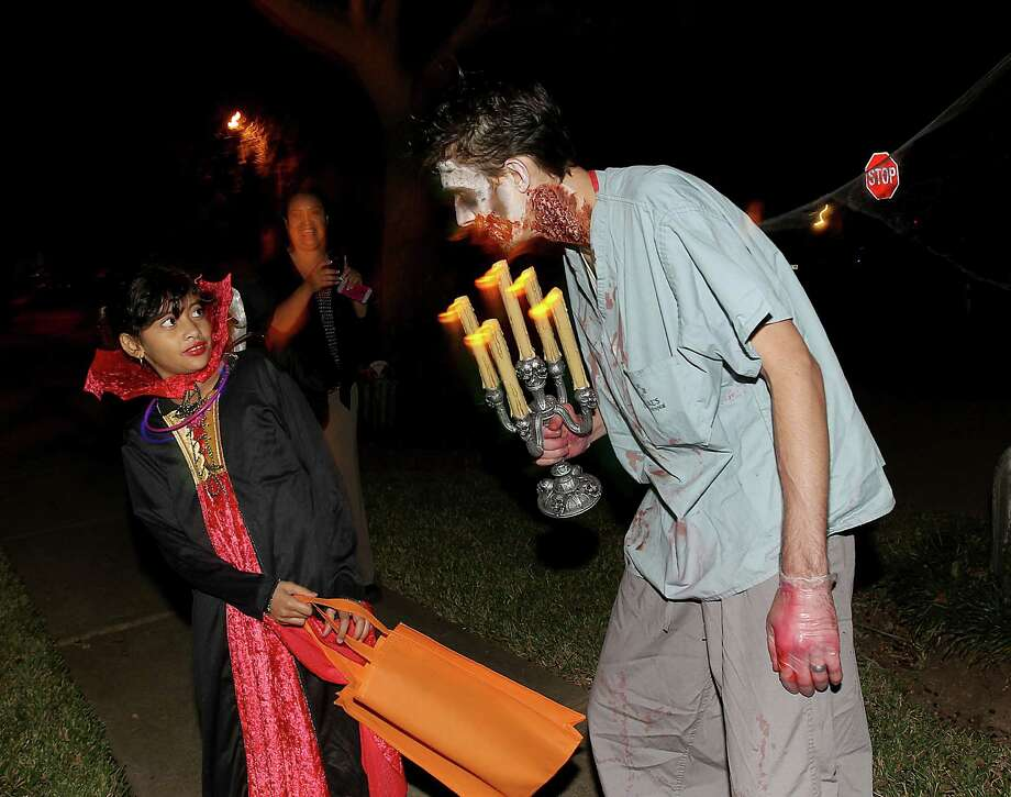 Rachel Philips, 9, leans away from Clayton Dorsey, in his yard as she trick-or-treated in the New Territory subdivision on Halloween night, Wednesday, Oct. 31, 2012, in Sugar Land. Photo: Karen Warren, Houston Chronicle / © 2012  Houston Chronicle