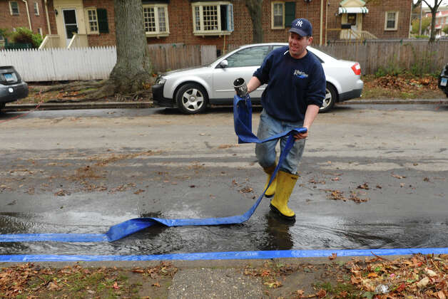 Chris Seneca, of East Coast Plumbing and Drain, works to remove water from flooded basements because of hurricane Sandy at Seaside Village in Bridgeport, Conn. on Wednesday October 31, 2012. Photo: Christian Abraham, Connecticut Post / Connecticut Post