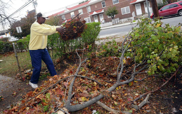 To make a few dollars, Gene Dawson, of Waterbury, cleans up the yard of a Seaside Village resident from damage left behind by Hurricane Sandy at the village in Bridgeport, Conn. on Wednesday October 31, 2012. Photo: Christian Abraham, Connecticut Post / Connecticut Post