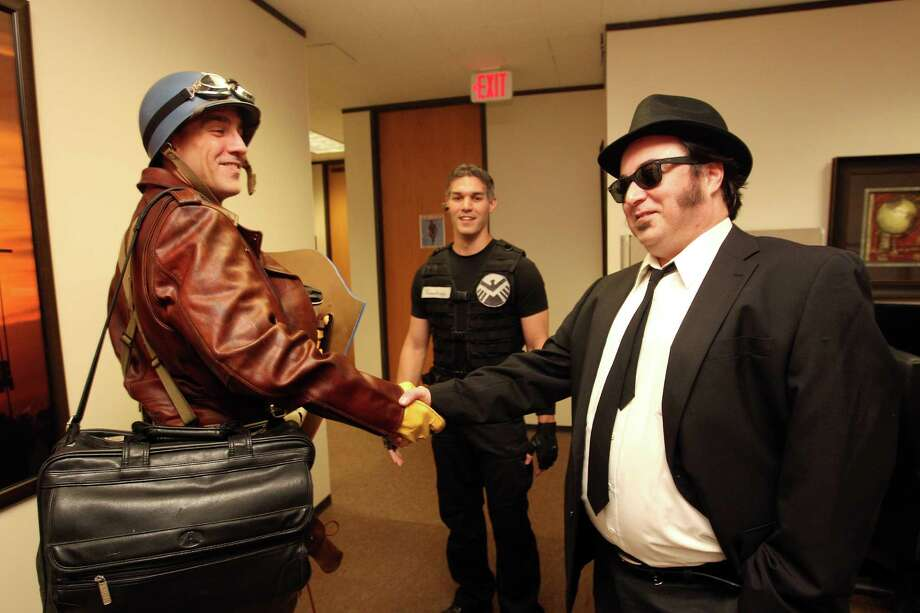 "Dressed as Captain America from the movie Captain America: The First Avenger, Chauncey Roschbach, a senior information technology manager at a oil and gas equipment online auction company greets his co-workers, David Shepherd, right, dressed as ""Joliet"" Jake Blues from the movie the Blues Brothers and Clint Akin who is dressed as Hawkeye from the movie The Avengers Friday, Oct. 26, 2012, in Houston. Photo: Johnny Hanson, Houston Chronicle / © 2012  Houston Chronicle"
