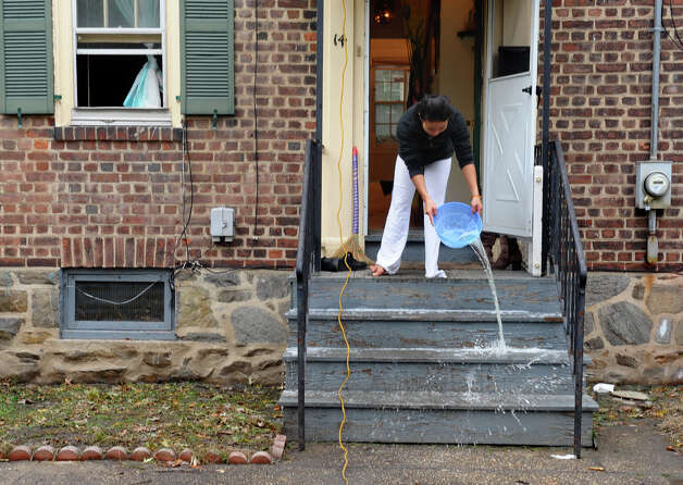 Seaside Village resident Tin Thach tosses out water she was using to disinfect her floors from damage left behind by Hurricane Sandy at the village in Bridgeport, Conn. on Wednesday October 31, 2012. Photo: Christian Abraham, Connecticut Post / Connecticut Post