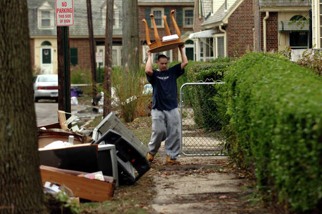Seaside Village resident Teddy Morales goes to throw out furniture that was in his flooded basement due to Hurricane Sandy at the village in Bridgeport, Conn. on Wednesday October 31, 2012. Photo: Christian Abraham, Connecticut Post / Connecticut Post