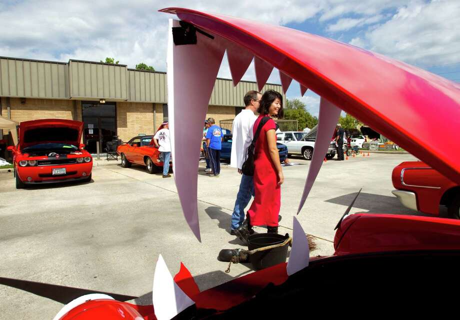 Christie Heiser and Jay Smith walk past a 1984 Porsche adorned with fangs during the 5th Annual Halloween Classic car show at the National Museum of Funeral History Saturday, Oct. 20, 2012, in Houston. Photo: Brett Coomer, Houston Chronicle / © 2012 Houston Chronicle