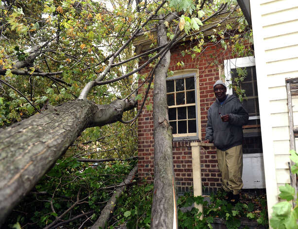 Seaside Village resident James Brown stands on his back porch where a very large tree has fallen down next to and was a result of Hurricane Sandy at the village in Bridgeport, Conn. on Wednesday October 31, 2012. Photo: Christian Abraham, Connecticut Post / Connecticut Post