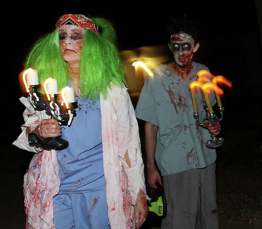 Patty Dorsey, left and her son, Clayton Dorsey dressed as zombies for the trick-or-treaters in their New Territory subdivision on Halloween night, Wednesday, Oct. 31, 2012, in Sugar Land. Photo: Karen Warren, Houston Chronicle / © 2012  Houston Chronicle