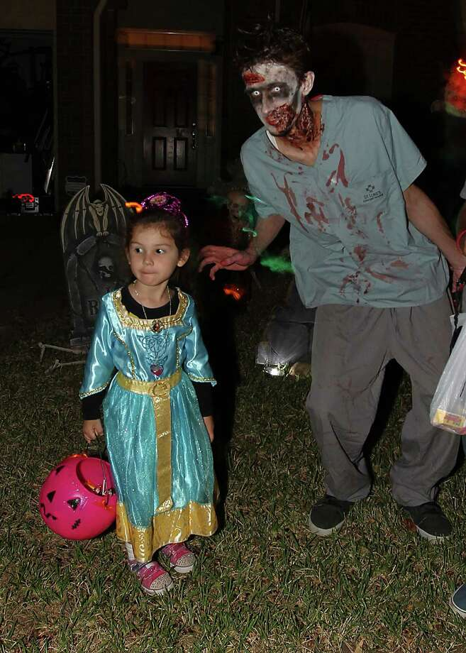 Clayton Dorsey dressed as a zombie for the trick-or-treaters tries to scare Victoria Staley, 4, in front of his house in the New Territory subdivision on Halloween night, Wednesday, Oct. 31, 2012, in Sugar Land. Photo: Karen Warren, Houston Chronicle / © 2012  Houston Chronicle