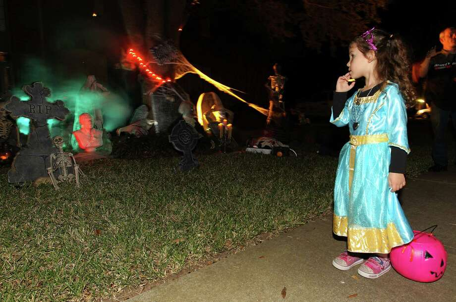 Victoria Staley, 4, is captivated by the cemetery scene in front of a house in the New Territory subdivision on Halloween night, Wednesday, Oct. 31, 2012, in Sugar Land. Photo: Karen Warren, Houston Chronicle / © 2012  Houston Chronicle