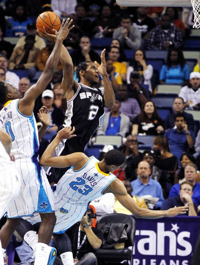 San Antonio Spurs small forward Kawhi Leonard (2) shoots over New Orleans Hornets power forward Anthony Davis (23) as Davis draws an offensive foul in the first half of an NBA basketball game in New Orleans, Wednesday, Oct. 31, 2012. (AP Photo/Gerald Herbert) (Associated Press)