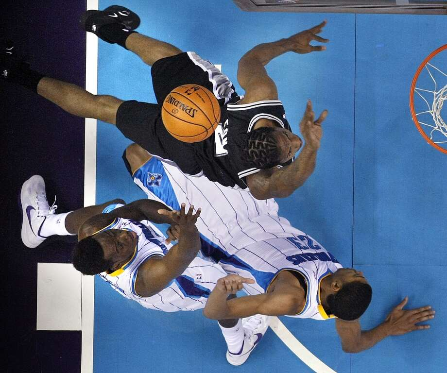 San Antonio Spurs small forward Kawhi Leonard drives to the basket against a falling New Orleans Hornets power forward Anthony Davis (23) in the first half of an NBA basketball game in New Orleans, Wednesday, Oct. 31, 2012. Bottom left is small forward Al-Farouq Aminu. (AP Photo/Gerald Herbert) (Associated Press)