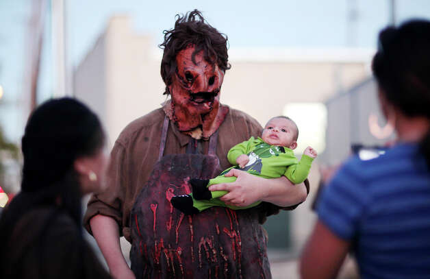 Krixuz Jimenez, 2, (cq), gets his photo taken with Leatherface a character from the movie The Texas Chainsaw Massacre, played by Marc Matthesson,  as one of the last crowds gathers forNightmare on Grayson, Wednesday, Oct. 31, 2012. The event is schedule to move out of the East Grayson Street location for the next run. The last two nights will be Friday and Saturday. Photo: Jerry Lara, San Antonio Express-News / San Antonio Express-News