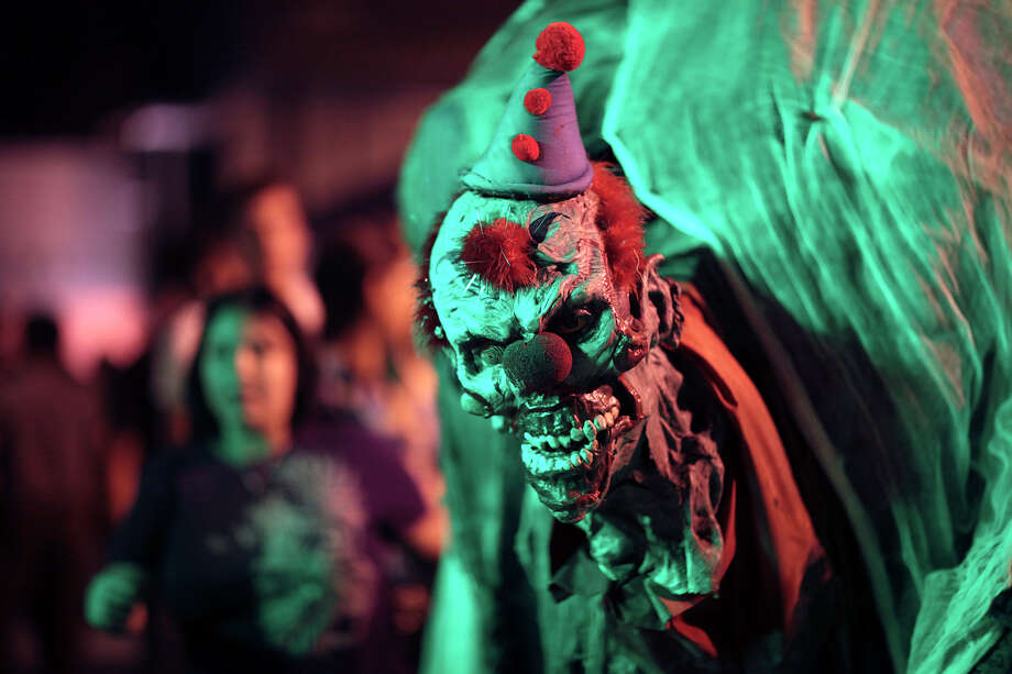 Squeaky the Clown participates in a line dance as one of the last crowds gathers at Nightmare on Grayson, Wednesday, Oct. 31, 2012. The event is schedule to move out of the East Grayson Street location for the next run. Photo: Jerry Lara, San Antonio Express-News / San Antonio Express-News