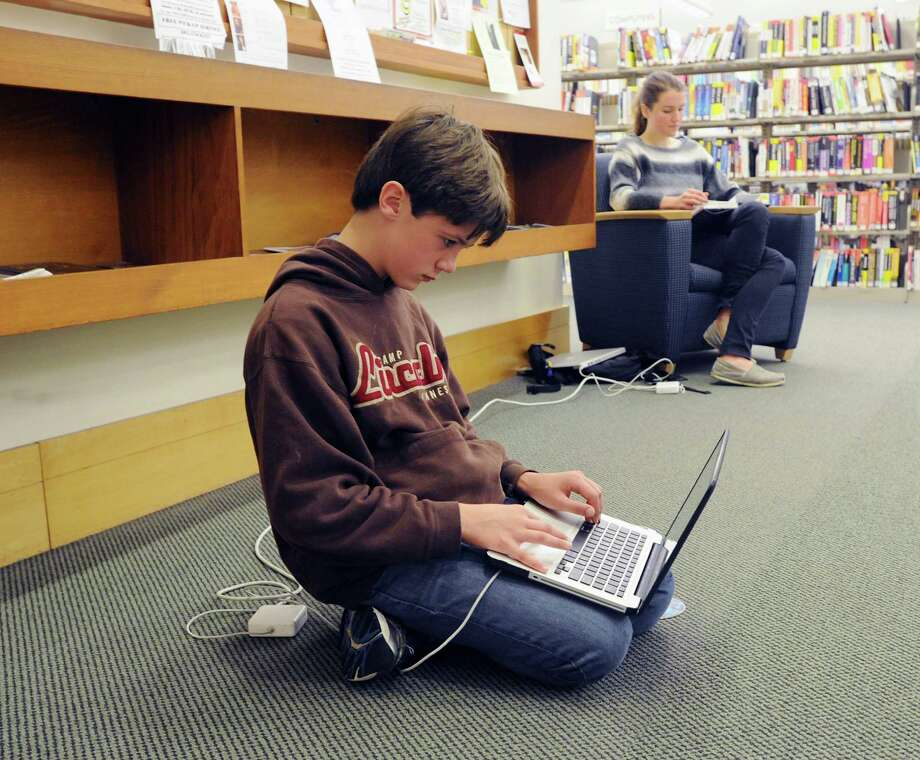 Wiliam Dunn, 12, of Greenwich, plugged in and using the internet at Greenwich Library, Wednesday morning, Oct. 31, 2012. Dunn and much of Greenwich are still without electricity due to Hurricane Sandy making the  library and its amenities have become a gathering spot for the community. Photo: Bob Luckey / Greenwich Time