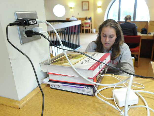 Heather Desino, 16, of Greenwich, plugged in and using the internet at Greenwich Library, Wednesday morning, Oct. 31, 2012. Desino and much of Greenwich are still without electricity due to Hurricane Sandy making the  library and its amenities have become a gathering spot for the community. Photo: Bob Luckey / Greenwich Time