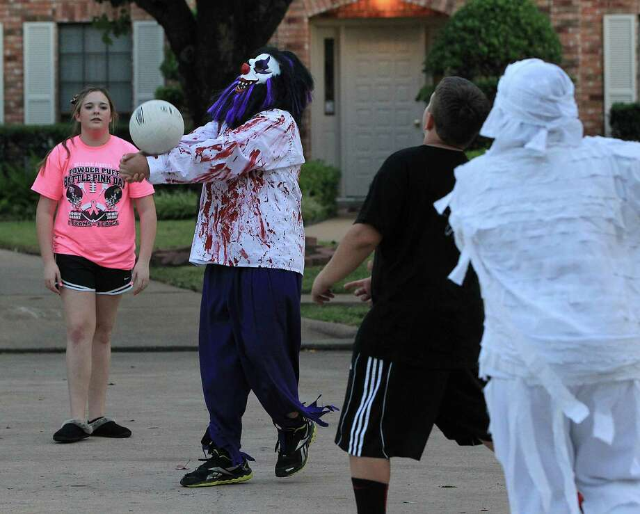 Jake Myers, 12, dressed as a bloody clown, plays volleyball in the street with friends before heading out for a night of trick-or-treating in the New Territory subdivision on Halloween night, Wednesday, Oct. 31, 2012, in Sugar Land. Photo: Karen Warren, Houston Chronicle / © 2012  Houston Chronicle