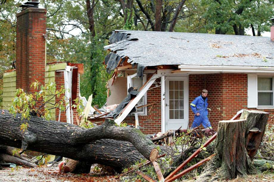 FILE - In this Tuesday, Oct. 30, 2012 file photo, a firefighter leaves the destroyed home in Pasadena, Md where Donald Cannata Sr. was killed overnight when a tree fell on it during superstorm Sandy. (AP Photo/Jose Luis Magana) Photo: Jose Luis Magana