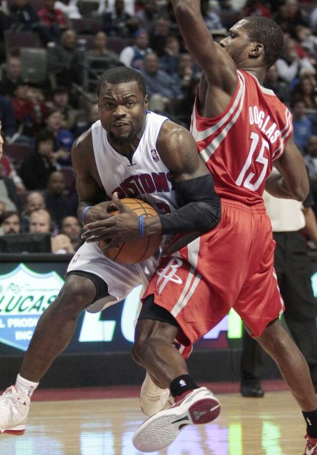 Pistons guard Will Bynum, left, collides with Rockets guard Toney Douglas (15) while driving to the basket. (Duane Burleson / Associated Press)