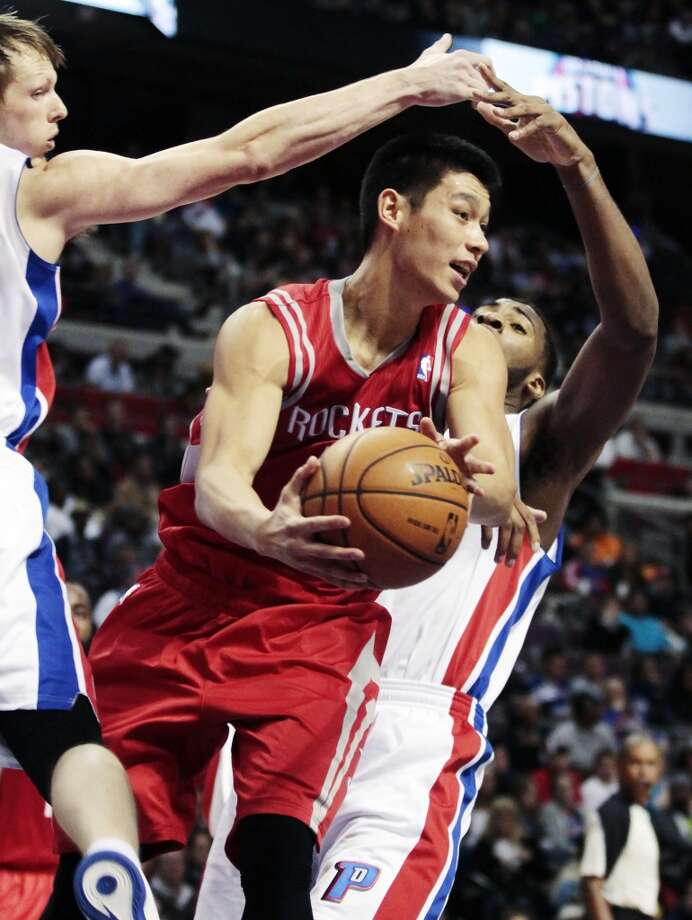 Jeremy Lin is forced to pass the ball against the defensive play of Pistons forward Kyle Singler, left, and forward Andre Drummond, right. (Duane Burleson / Associated Press)