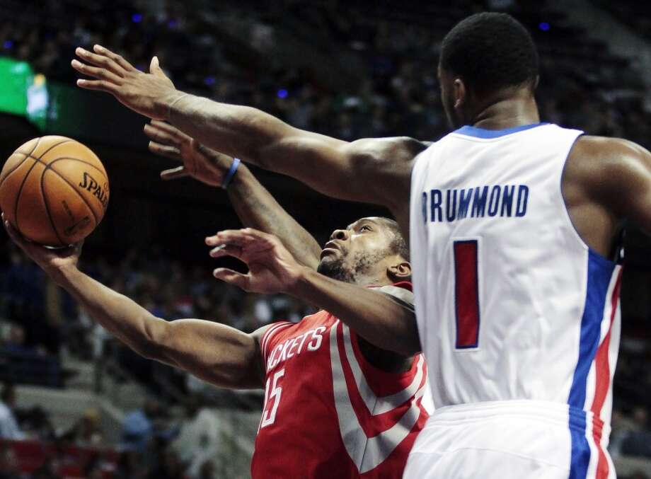 Rockets guard Toney Douglas (15) goes to the basket against Pistons forward Andre Drummond. (Duane Burleson / Associated Press)