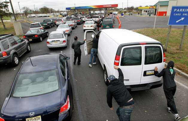 People help push John Oh's van to the pumps at the New Jersey Turnpike's Thomas A. Edison service area Wednesday, Oct. 31, 2012, near Woodbridge, N.J., after Oh, of Blue Bell, Pa., ran out of gas waiting in a long line near exit 11. After Monday's storm surge from Sandy, many gas stations in the region are without power and those that are open have very long lines. Photo: Mel Evans, Associated Press / AP