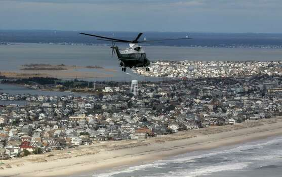Marine One with US President Barack Obama on board flies over damage area in Seaside Heights, New Jersey, on October 31, 2012. Americans sifted through the wreckage of superstorm Sandy on Wednesday as millions remained without power. The storm carved a trail of devastation across New York City and New Jersey, killing dozens of people in several states, swamping miles of coastline, and throwing the tied-up White House race into disarray just days before the vote. Photo: DOUG MILLS, AFP/Getty Images / AFP