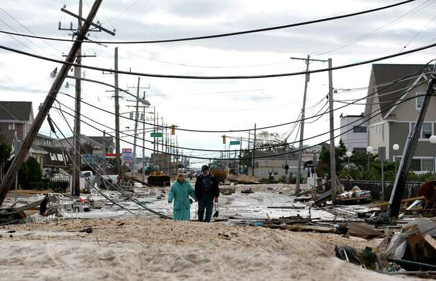 Robert Bryce, right, walks with his wife, Marcia Bryce, as destruction from superstorm Sandy is seen on Route 35 in Seaside Heights, N.J., Wednesday, Oct. 31, 2012. Sandy, the storm that made landfall Monday, caused multiple fatalities, halted mass transit and cut power to more than 6 million homes and businesses. Photo: Julio Cortez, Associated Press / AP