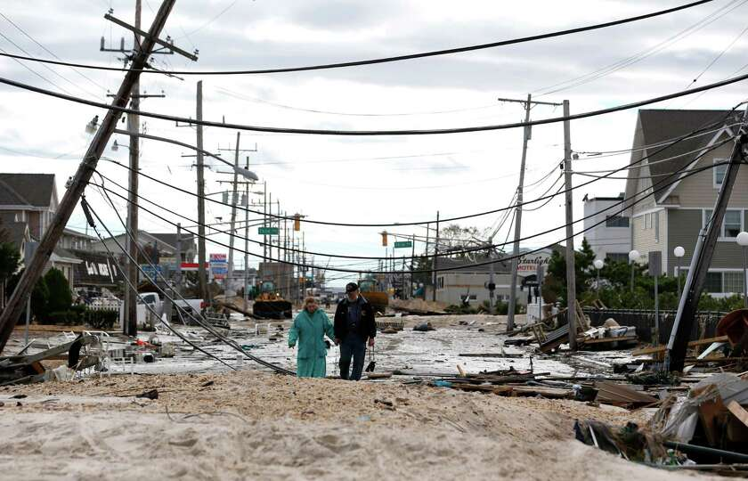 Robert Bryce, right, walks with his wife, Marcia Bryce, as destruction from superstorm Sandy is seen