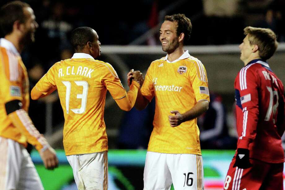 Houston Dynamo midfielder Adam Moffat (16) celebrates with midfielder Ricardo Clark (13) against the Chicago Fire after their MLS soccer playoff match, Wednesday, Oct. 31, 2012, in Bridgeview, Ill. Houston won 2-1. (AP Photo/Nam Y. Huh) Photo: Nam Y. Huh, Associated Press / AP
