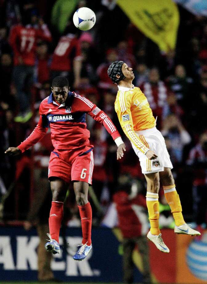 Houston Dynamo forward Calen Carr, right, and Chicago Fire defender Jalil Anibaba (6) battle for the ball during the second half of their MLS soccer playoff match, Wednesday, Oct. 31, 2012, in Bridgeview, Ill. Houston won 2-1. (AP Photo/Nam Y. Huh) Photo: Nam Y. Huh, Associated Press / AP