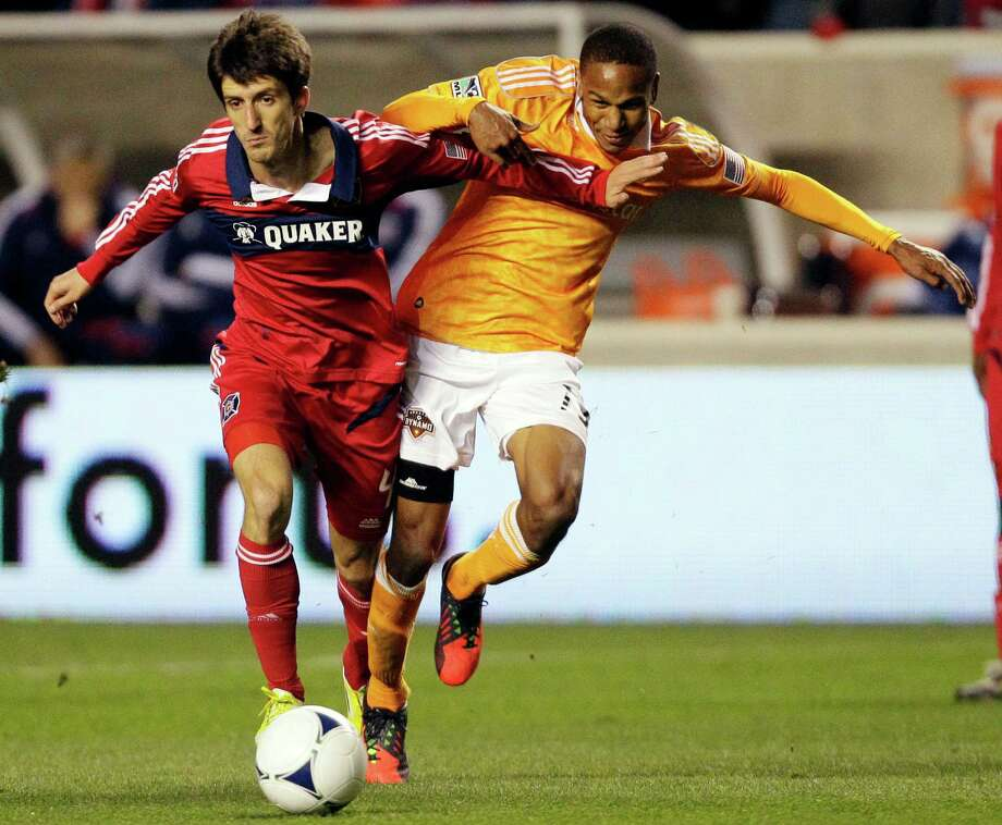 Chicago Fire midfielder Alvaro Fernandez, left, and Houston Dynamo midfielder Ricardo Clark (13) battle for the ball during the first half of their playoff MLS soccer match, Wednesday, Oct. 31, 2012, in Bridgeview, Ill. (AP Photo/Nam Y. Huh) Photo: Nam Y. Huh, Associated Press / AP